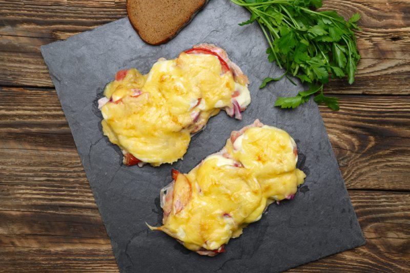 Свиные отбивные, украшенные сыром и томатом