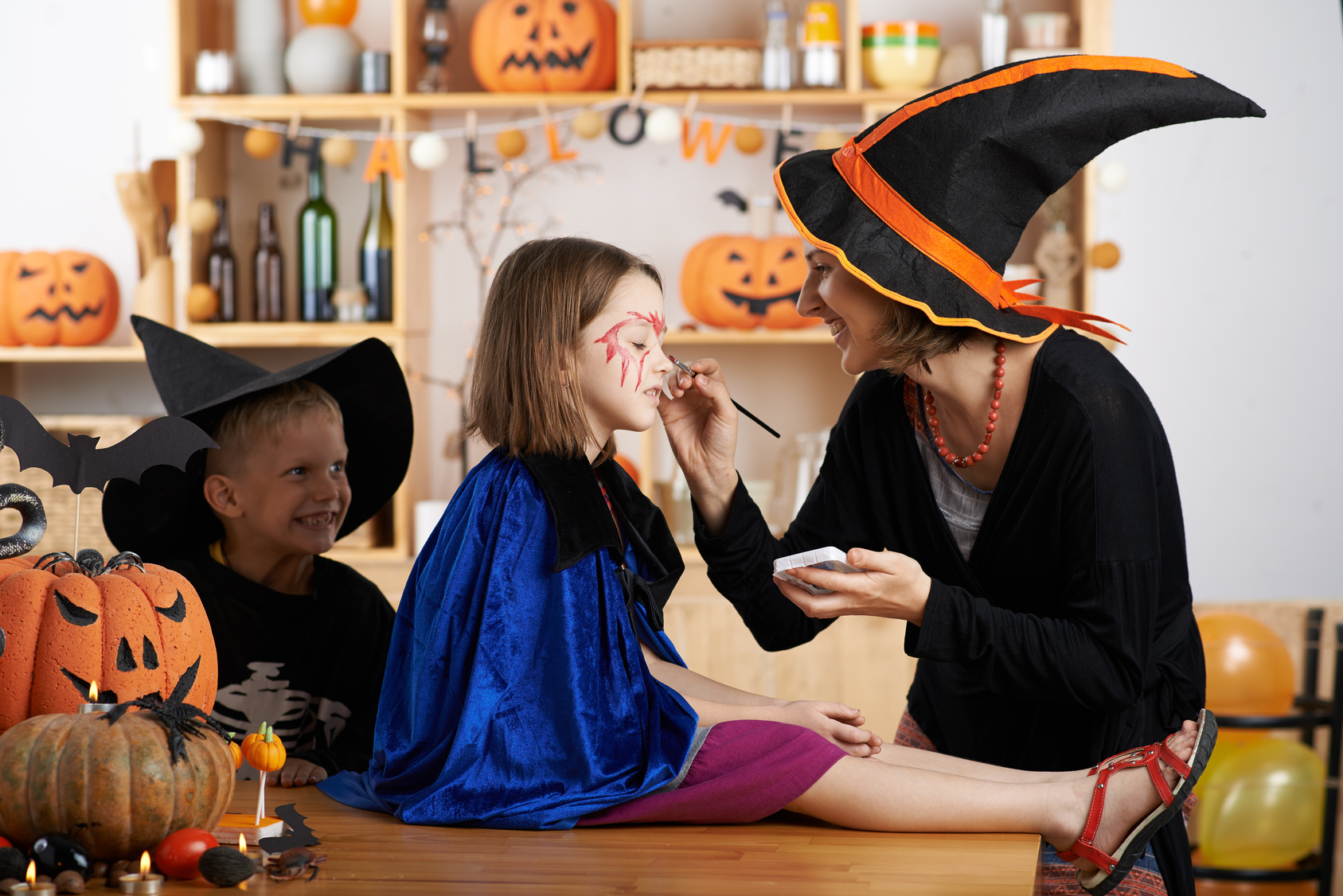 Teacher painting face of little girl for Halloween celebration