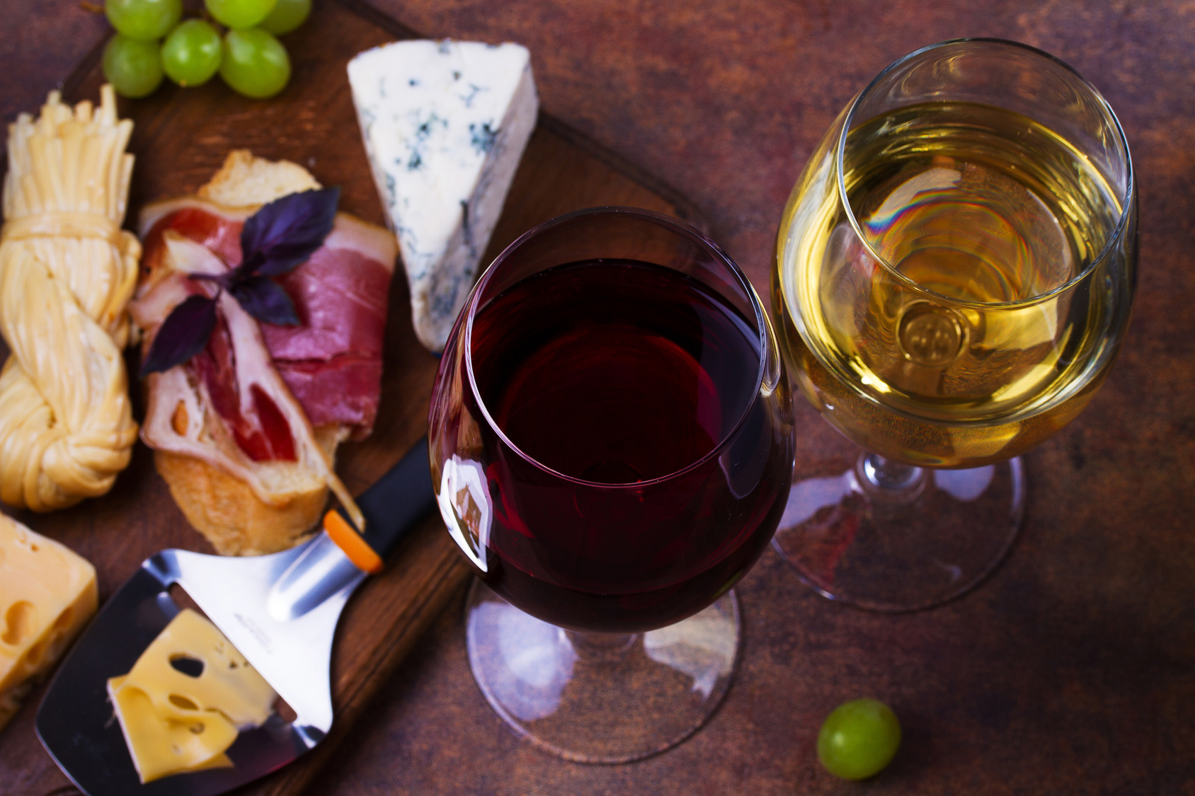 Red and white wine. Smoked cheese, grape, prosciutto, garlic and bread. View from above, top studio shot