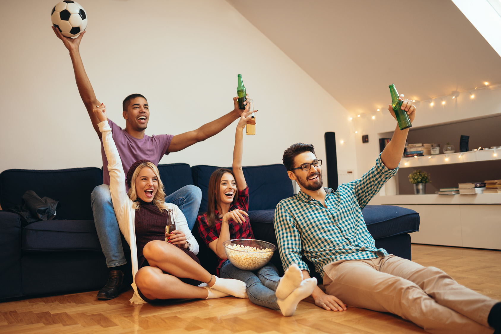 Photo of a group of friends watching football and drinking beer.