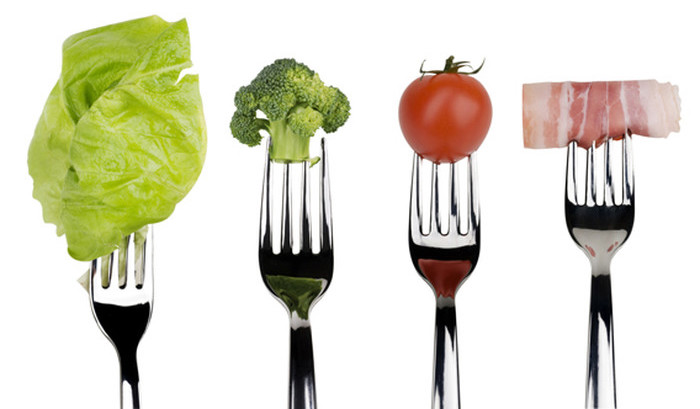 Broccoli, tomato, lettuce salad and slice of bacon on forks isolated on a white background.