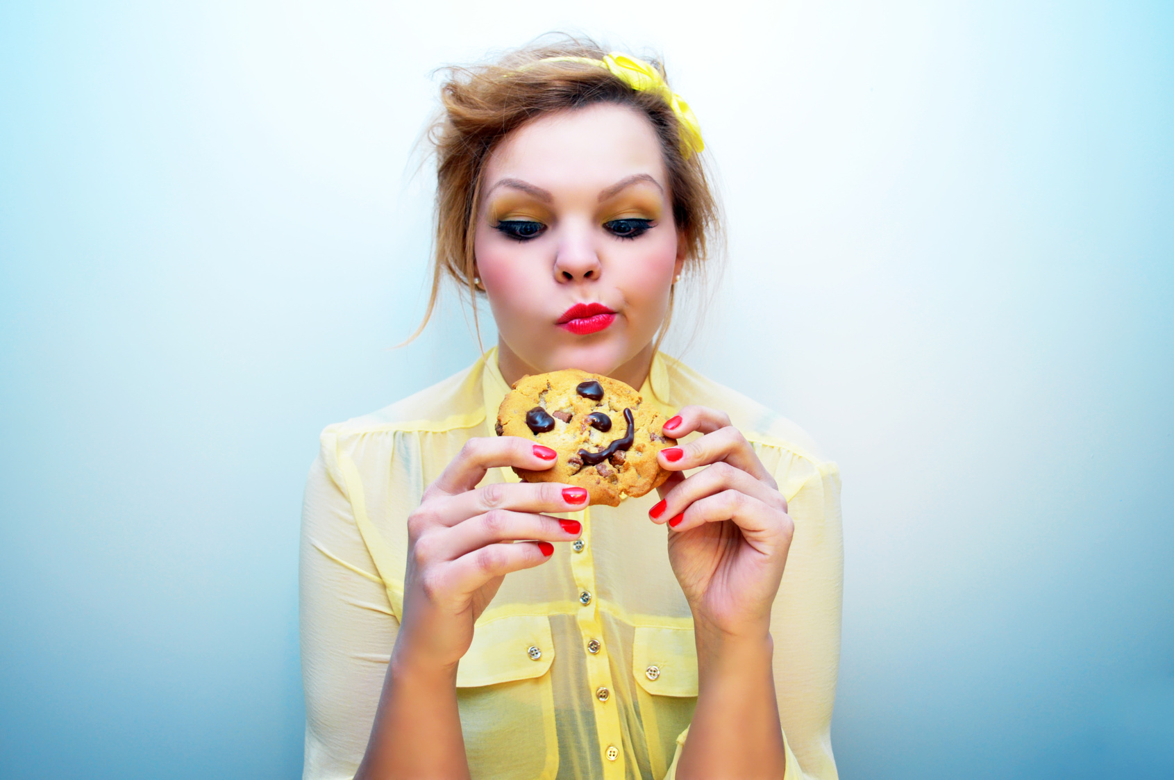 Trendy young woman is eating a smiling chocolate chip cookie.